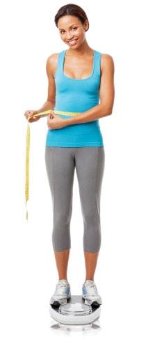 fit light brown skinned woman measuring waistline
