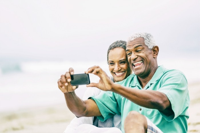 Senior African American couple having fun photographing self portrait with smartphone on sandy beach.